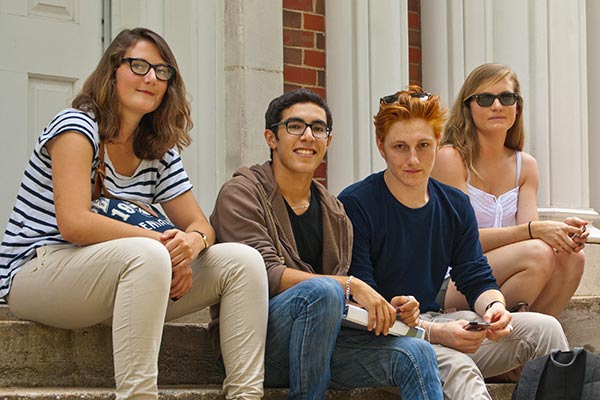 4 students sitting on step - links to international student resource page