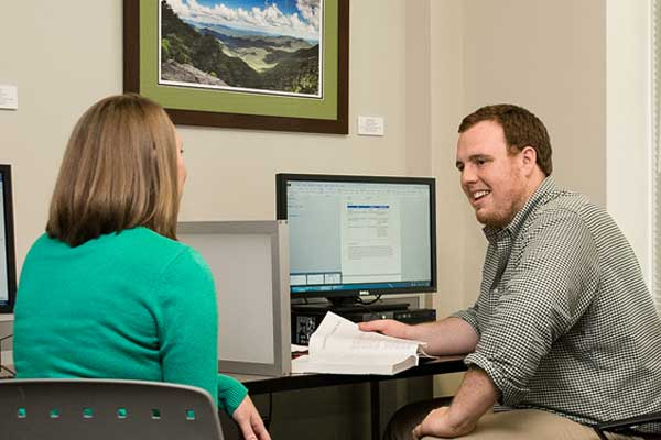 two people working at a computer - links to graduate studies site