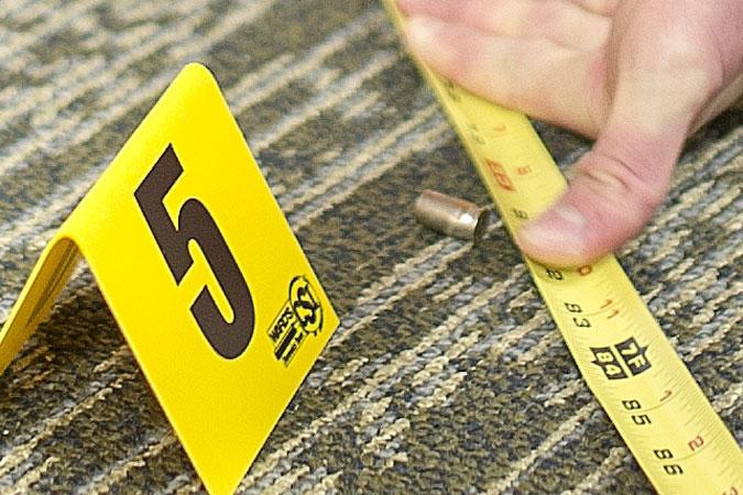 examining bullet cases on crime scene