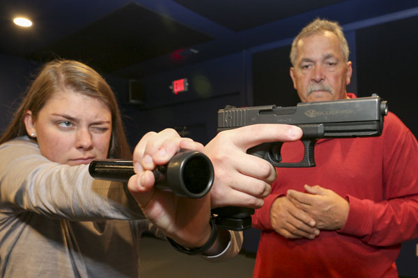 Alexis Sutton, a junior from Newnan, Georgia, takes aim with a replica handgun in UNG's new high-tech simulator while Dr. Butch Newkirk, an assistant professor of criminal justice at UNG, looks on.