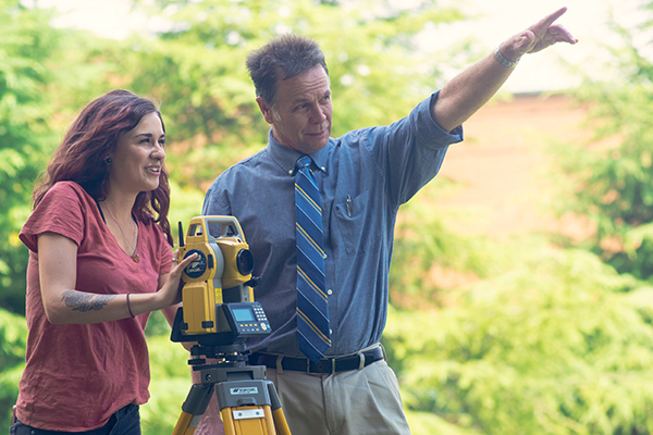Student Logan Moore operates a total station surveyor with Dr. Jeff Turk, IESA director