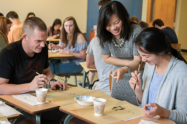 Instructor Yizhe Huang looks at student's effort at painting Chinese art during a class at the Summer Language Institute.