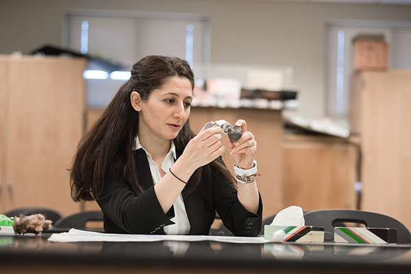 Dr. Katayoun Mobasher, associate professor of geology and recipient of a 2017 Presidential Semester Incentive Award, examines a rock with a magnifying glass, an important process in studying geology that can prove difficult for students with visual disabilities. Using her award, she plans to remedy these challenges.