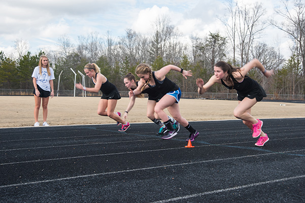 (From left to right): Runners Sarah Noel Whittington, Mary Owen Howell, Kelly Hayde, and Elizabeth Mullenax push off from the starting line as they practice sprints leading up to the track and field team's first competition on Feb. 26.