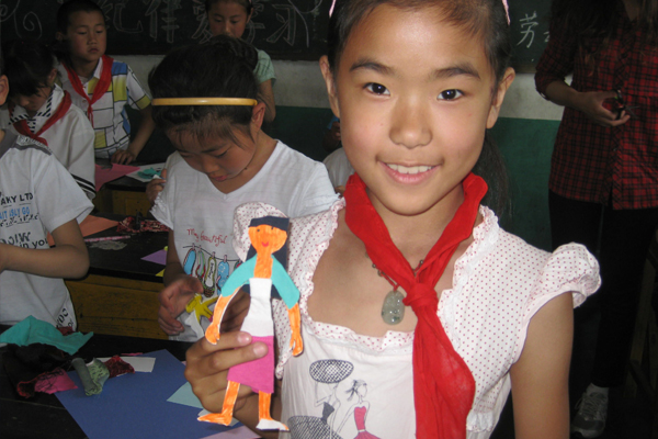 A young girl shows a paper doll she made during classes with aspiring teachers from UNG's College of Education during a study abroad trip to China.