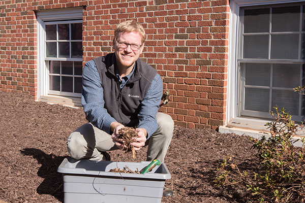 UNG's Environmental Leadership Center director Dr. Justin Ellis places mulch on areas of the ground that lacks nutrition or are dead to restore it back to health in the Community Garden on the Dahlonega Campus.