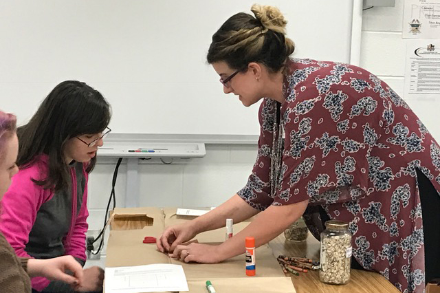 Katie Hilton (right), who is majoring in middle grades education, helps a Fannin County High School student make a seed packet for heirloom sunflowers.
