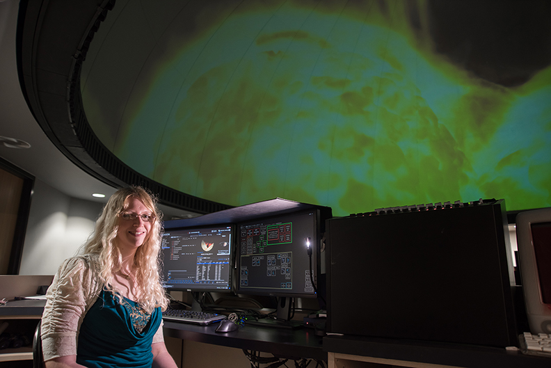 Dr. Lesley Simanton-Coogan, director of the George E. Coleman Sr. Planetarium at UNG and a lecturer in physics, sits in the planetarium with an image of the sun projected in the background.