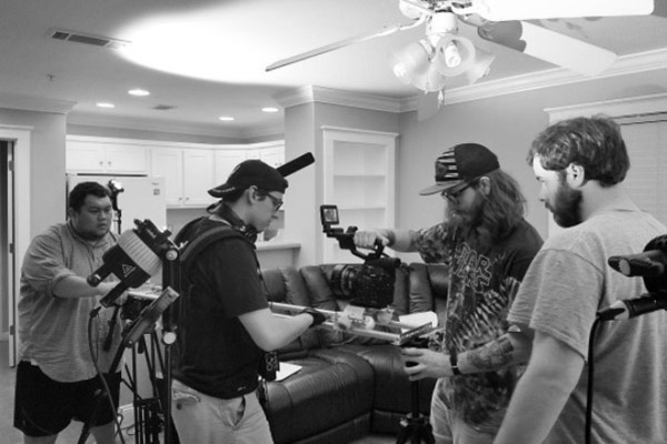UNG students Jeremy Thao, writer and director; Tyler Calder, sound recordist and audio mixer; Tylere Brown, director of photography; and Brandon Adams, first AC and key grip set up a scene for their award winning short-film.