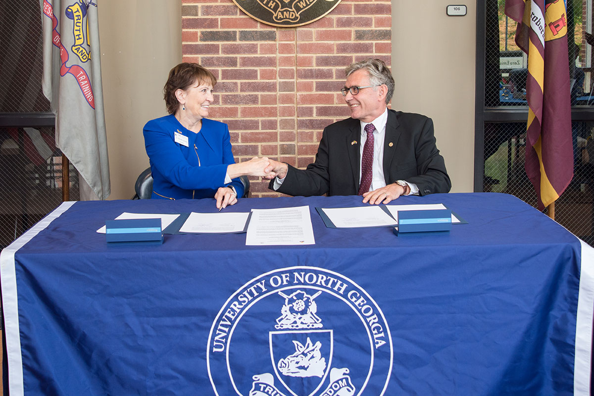 UNG President Bonita Jacobs, left, shakes hands with Willem de Villiers, rector and vice-chancellor of Stellenbosch University, after the two signed an agreement creating a new partnership between the two schools.
