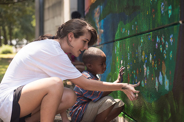 UNG art student Melanie Mitchell shows 5-year-old Junior how to use his fingers to paint on a mural. Mitchell and Michelle Vatral are interning at the Gainesville Housing Authority (GHA) with the purpose of creating a mural visible to residents of Melrose Apartments.