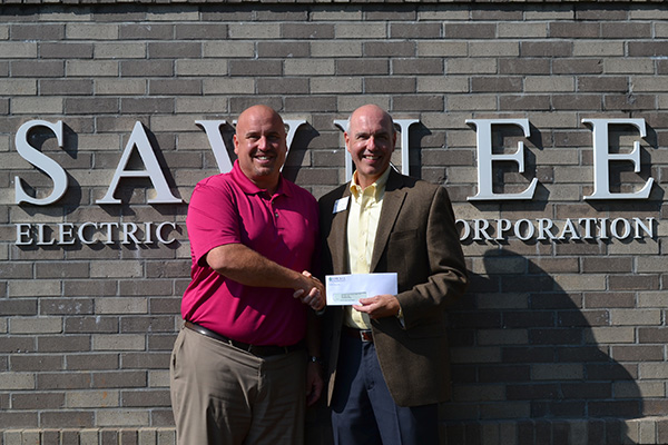 Blake House, vice president for marketing and member services at Sawnee EMC, hands Jason Pruitt, executive director of UNG Cumming Campus a $10,000 check to be used for student scholarships.