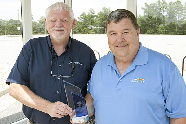 Bill Moody, director of Facilities and Operations for UNG's Gainesville, Cumming and Oconee campuses, and Stan Brown, city manager of Oakwood, display award for the park and ride lot and Sidewalk Innovation Project off exit 17 off Interstate 985 in Oakwood.