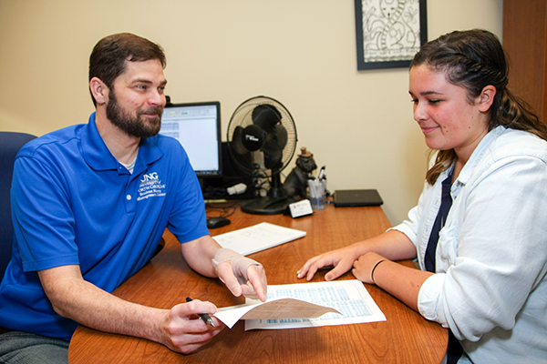 Erick Jones, the Student Money Management Center (SMMC) director, advises University of North Georgia (UNG) student Lea Presley in his office on the UNG Dahlonega Campus. The SMMC's services are available to all students on all five campuses.