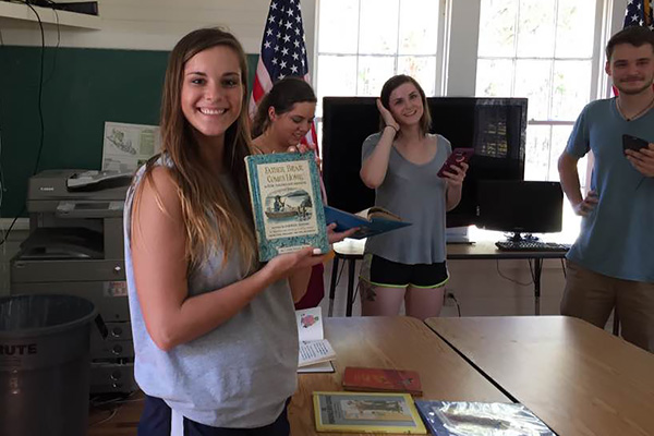 UNG student Kristina Freeman (with book), and students (left to right) Jenna Davidson, Heidi Martin, and Cameron Barker exploring a schoolhouse on Daufuskie Island.
