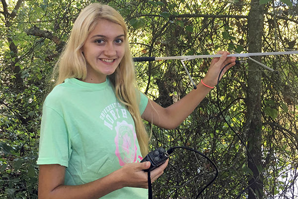 University of North Georgia (UNG) senior biology major Jessica Martin is holding a receiver and antennae, which are both pieces of equipment for radiotelemetry, to locate the Eastern box turtle in a wildlife area in Gainesville.