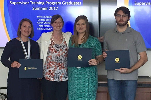 Elizabeth King, training and development specialist at UNG, second from left, gives Melissa Adams, from left, Kate Jordan and Aaron Chastain their certificates after completing the 2017 Supervisor Training Program. Lindsay Bailey and Emily McIllvain also completed the course but are not pictured.