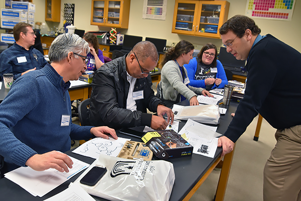 "Alfredo Hernandez, left and Roberto Rodriguez, from World Language Academy in Flowery Branch, in the ""The Art of Circuitry"" session with Dr. Mark Spraker, professor of physics at UNG, at the ELIPSE conference on Jan. 27."