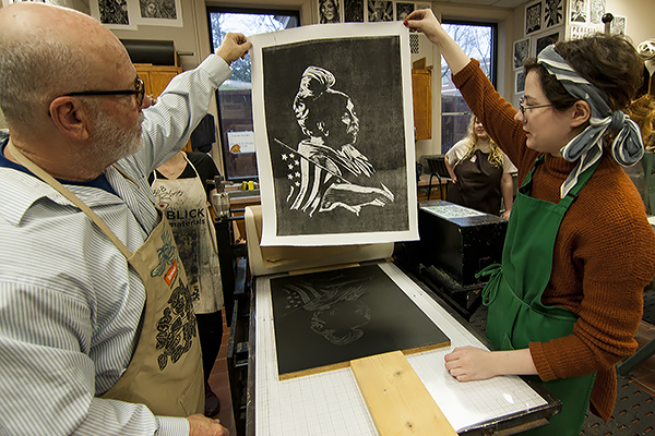 Michael Marling, professor of art, and Ashley Blair, a studio art major from Cleveland, Georgia, with a print of civil rights activist Fannie Lou Hamer, from a woodcut donated by Dr. Brian Mann,  head of the University of North Georgia's (UNG) Department of Modern & Classical Languages.