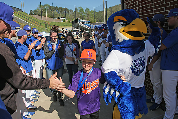 Chandler Holcomb, a 9-year-old from Gainesville battling leukemia, is escorted by UNG's Nigel the Nighthawk past student-athletes at the Coleman Field House as part of his Make-A-Wish celebration at Bob Stein Stadium on April 17.