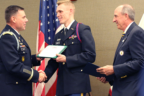 Cadet Col. Tyler Farney, center, commander of UNG's Boar's Head Brigade, is presented an award by Professor of Military Science Col. Joshua Wright, left, and Alan Ware, alumnus and president of the North Georgia Corps of Cadets Association. Farney is one of 21 UNG cadets named Distinguished Military Graduates.