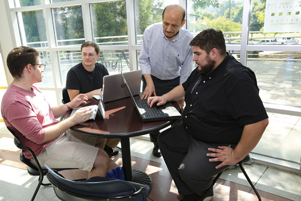 From left, students Darius Fiallo, Justin Frady and Deniz Keskin are conducting social media privacy research with Dr. Ahmad Ghafarian (standing), professor of computer science.