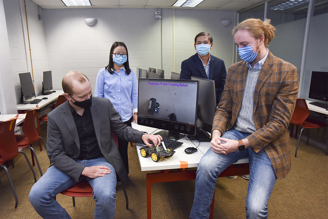 Students Justus Whitmire and Grayson Smith, seated, and faculty members Dr. Mingyuan Yan and Dr. Jianjun Yang have partnered on Internet of Things research.