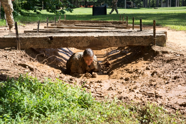 Dorottya Schneider, a visiting cadet from the National University of Public Service in Hungary, crawls through the mud on the Ranger Challenge course during FROG Week at UNG.