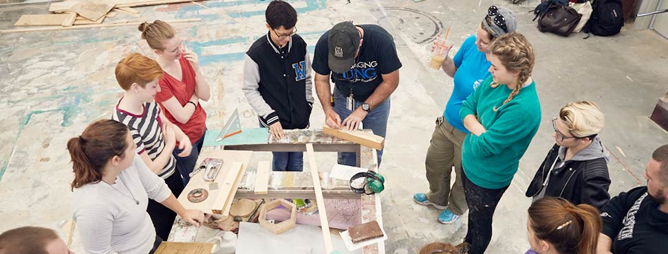 students in a set design class working with wood